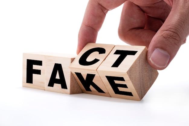 白い背景の上の「偽」から「事実」への文言の変更のための木製の立方体をめくる手。