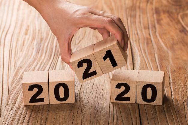 Рука переворачивает блок, меняющий 2020 год на 2021 год