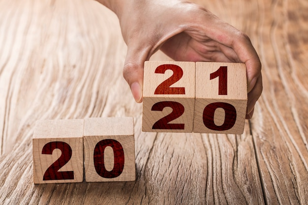 Hand flips a block changing 2020 to 2021