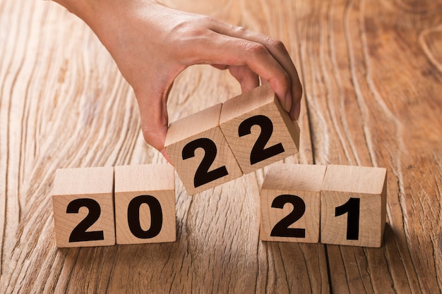 Hand flips a block changing 2021 to 2022