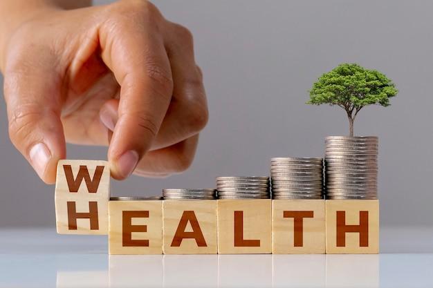 手は、成長するコインの山、生命保険への投資のアイデア、ヘルスケアのアイデアとともに、wealth forhealthという言葉で木製の立方体をひっくり返します。