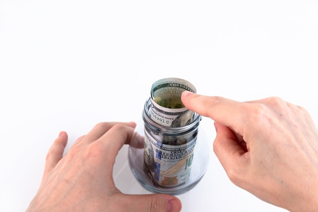 Hand folds paper american one hundred dollar bills, money in a glass jar. concept for making deposits, saving money. white background. copy space.