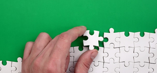 The hand folds a white jigsaw puzzle against the background of the green surface