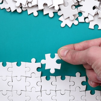 The hand folds a white jigsaw puzzle and a pile of uncombed puzzle pieces lies against the background of the blue surface.
