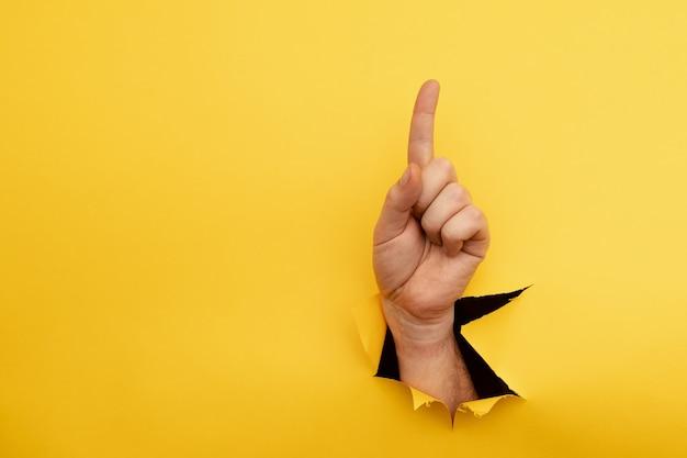 黄色の背景に分離された方向を示す手の人差し指