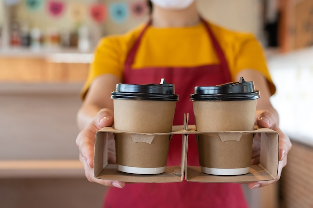 Дружелюбная к руке официантка в защитной маске для лица, ожидающая подачи чашки горячего кофе клиенту в кафе-кафе, кафе-ресторане, сервисном обслуживании, новой норме, концепции доставки еды и напитков