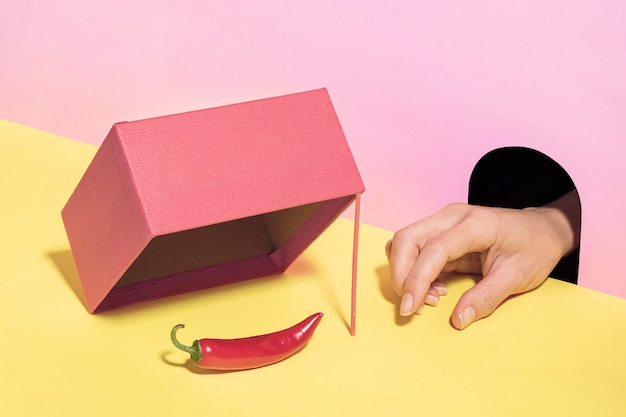 The hand from the burrow wants to steal the chili pepper from the trap. pastel surreal concept.