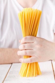 Рука полна сырых сухих спагетти, вид крупным планом