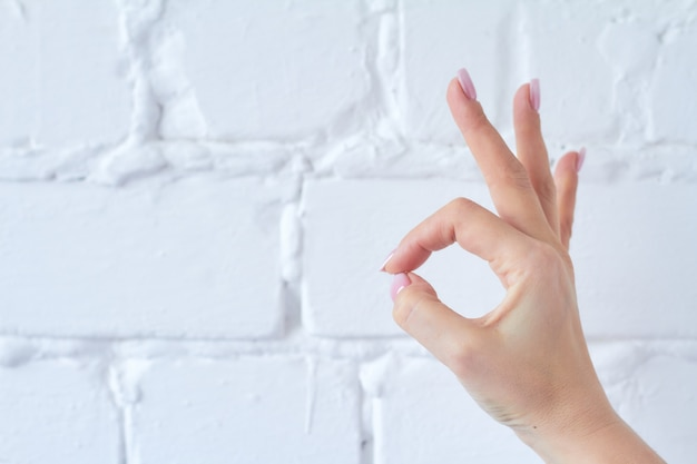 Hand gesture isolated on white brick wall background