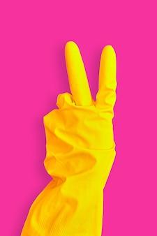 黄色のゴム手袋で手のジェスチャーの平和