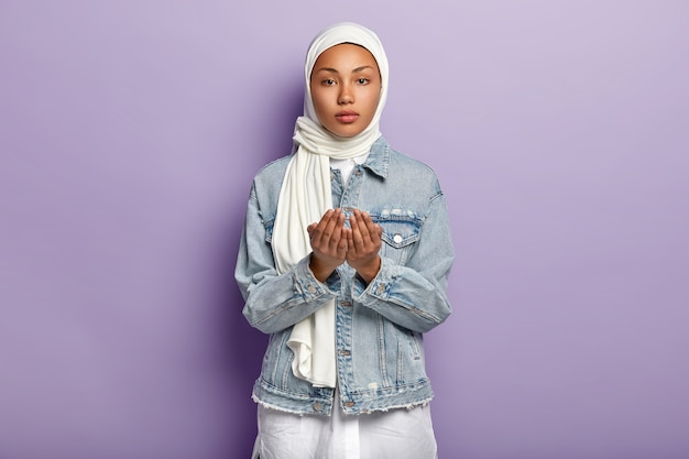 Hand gesture and praying concept. serious dark skinned female raises hands in prayer, pleads for something, wears scarf and denim jacket, isolated over purple wall. muslim religion concept