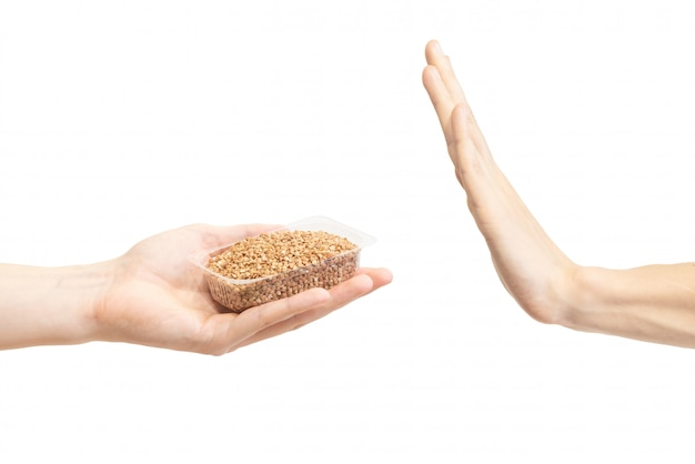 Hand gesture to reject proposal to eat brown buckwheat. Premium Photo