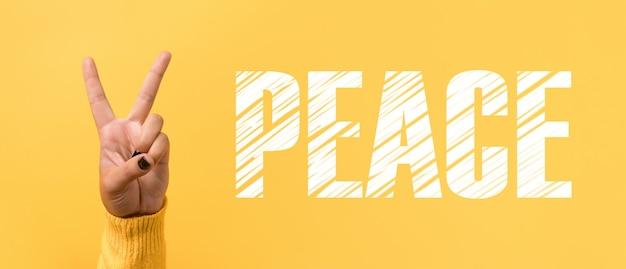 노란색 배경, 파노라마 이미지 위에 승리 또는 평화 기호를 위한 손 제스처 v 기호