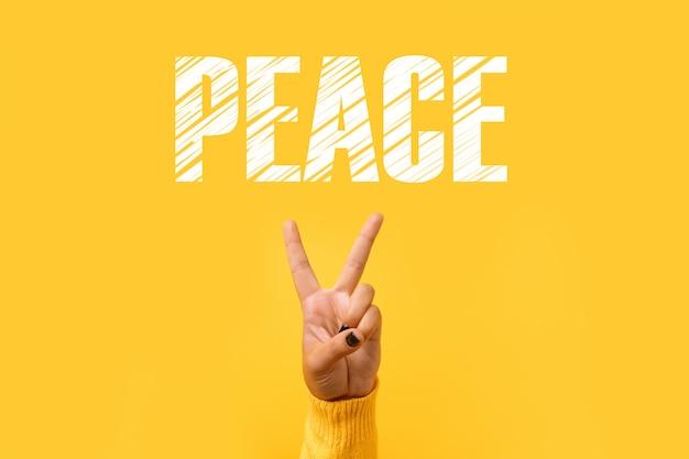 노란색 배경 위에 승리 또는 평화 기호를 위한 손 제스처 v 기호