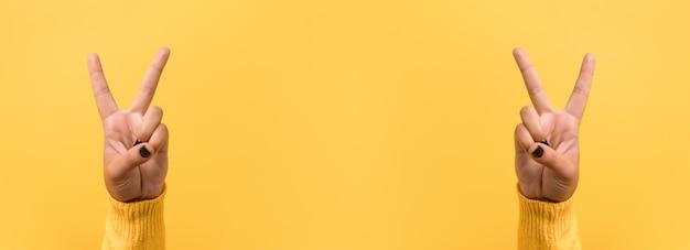 Жест рукой знак v для победы или знак мира над желтым