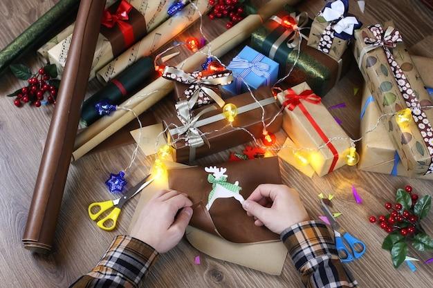 휴일 크리스마스 리본과 활을 위한 손 선물 포장지