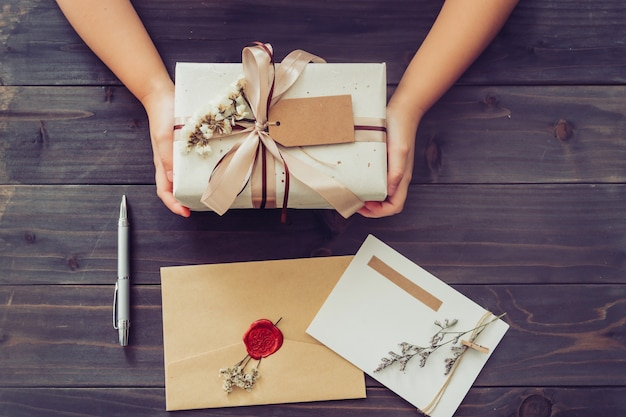 Above of hand girl present craft gift box with card and pen on wooden table background