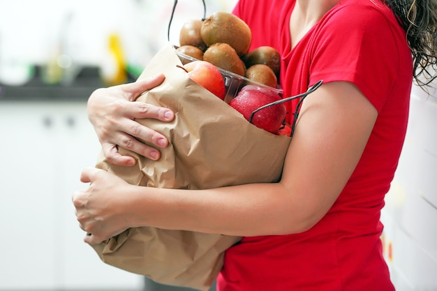 Hand of girl with bags of food at home.