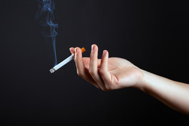 Hand of a girl with a cigarette and white smoke on a dark black background.