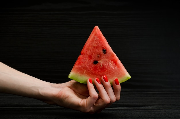 Hand girl with a triangular slice of watermelon