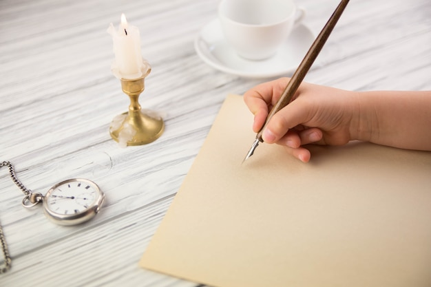 The hand of the girl writes with the ancient handle on paper