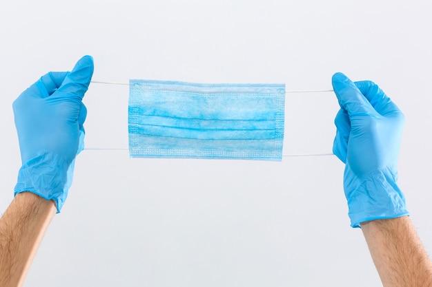 Рука дает хирургическую маску для защиты pm 2,5 и вируса короны, изолированного на белом фоне с обтравочным контуром