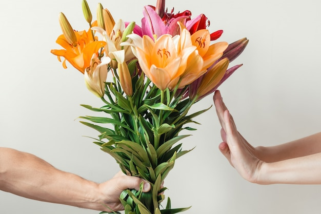 Hand gives bouquet of lilies flowers to girl, woman refuses and shows stop sign