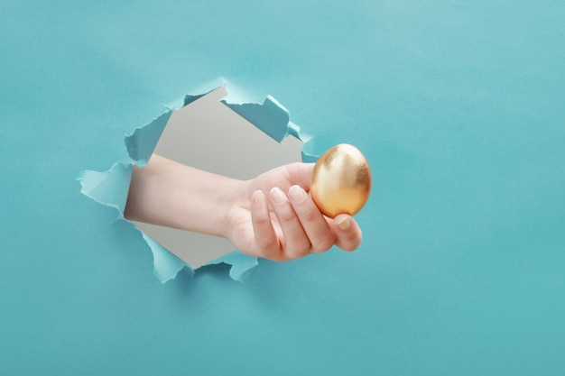 Hand gives golden egg through paper hole
