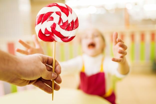 Рука дает счастливой маленькой девочке леденец ручной работы. дети в мастерской в кондитерской. праздничное развлечение в кондитерской. свежеприготовленная сахарная карамель