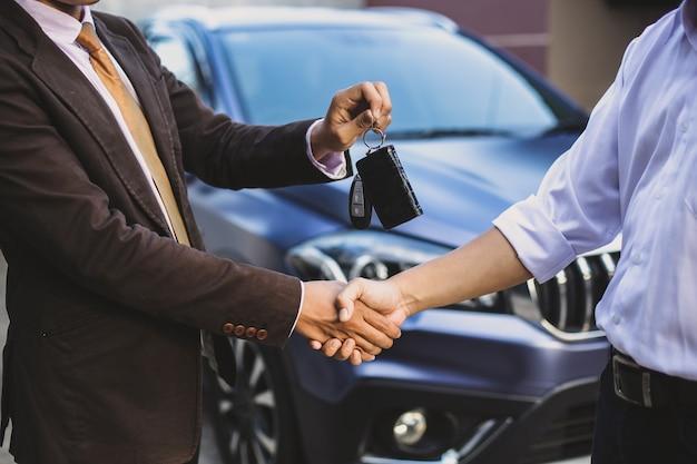 車の取引取引の概念のための握手で車のキーを与える手