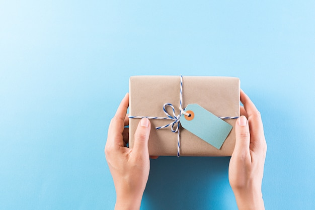 Рука, дающая подарочную коробку с поздравительной открыткой