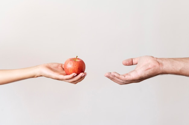 Hand giving apple fruit to needy person