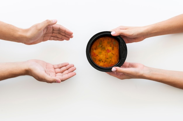 Hand giving bowl of soup to needy person