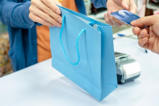 상점에서 직원 점원의 신용 카드 및 종이 봉지를주는 손