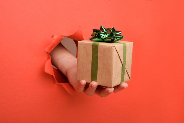 Hand giving gift box with kraft paper, through torn red paper wall. copy space aside for your advertising and offer or sale content.
