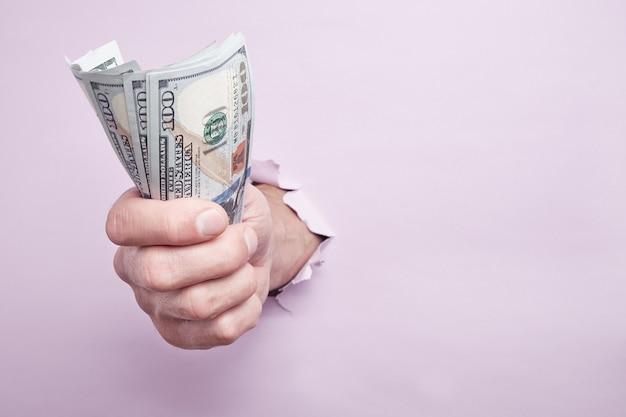 Hand giving money through a hole