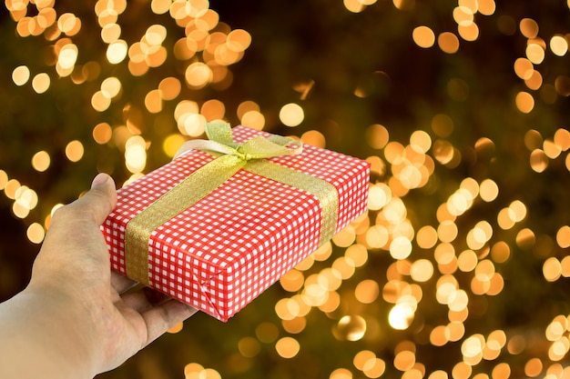Hand giving the red gift box