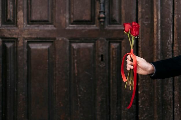 コピースペースで彼のカップルに赤いバラの花束を与える手