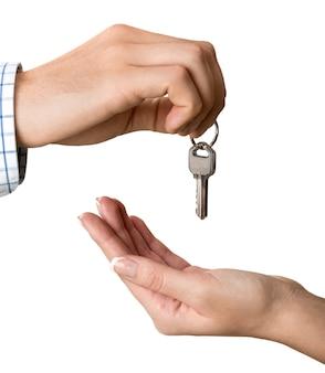 Hand giving set of house keys on light background