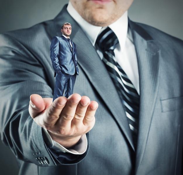 Рука дает небольшой уверенный бизнесмен