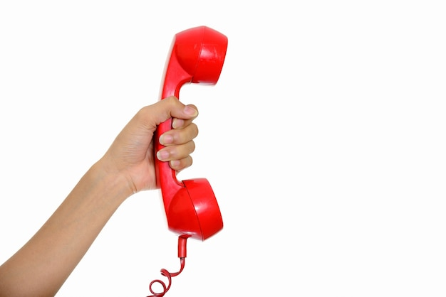 Hand giving telephone against white wall