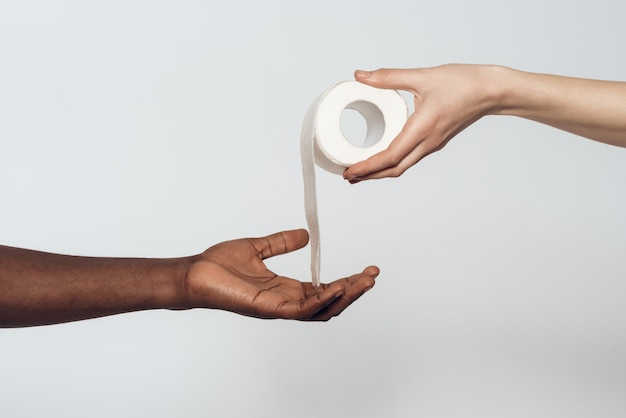 Hand giving toilet paper to black hand.