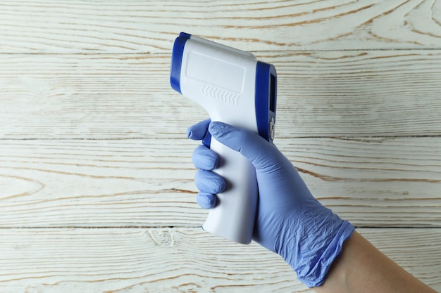 Hand in glove hold thermometer gun on white wooden