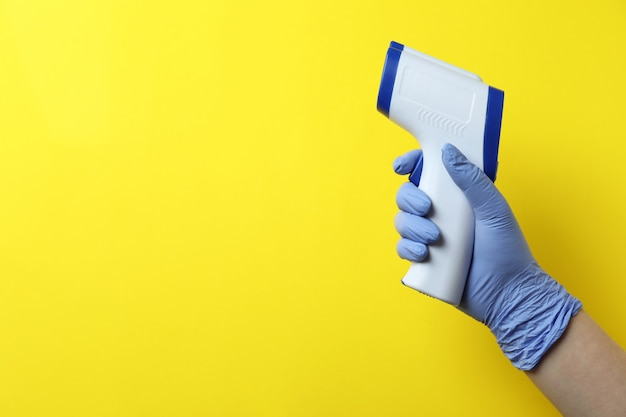 Hand in glove hold thermometer gun on yellow