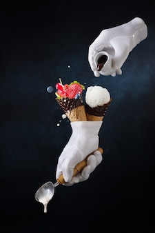 A hand in a glove holds an ice cream with berries. chocolate is poured onto the ice cream.