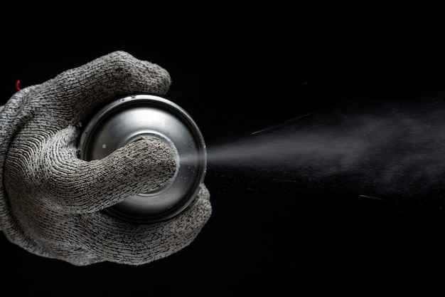 Hand in a glove holds a spray can on a black background. .
