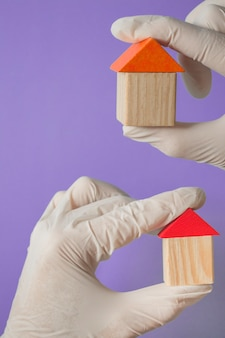 Hand in a glove holds a wooden house - concept of health insurance or family doctor banner, copy spice