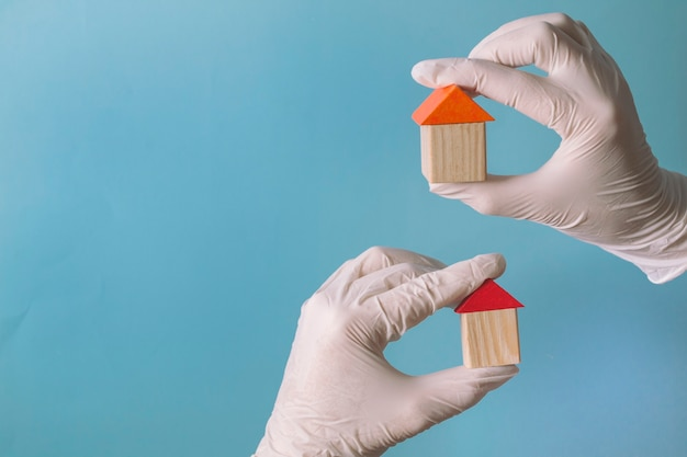 Hand in a glove holds a wooden house - concept of health insurance or family doctor
