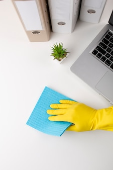 Hand in gloves cleaning desk