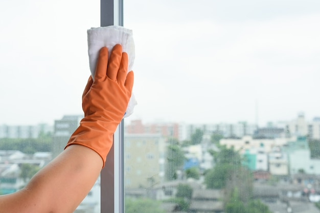 Hand in gloves cleaning window with rag and cleanser spray at home. housework